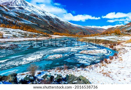 River valley in the snowy mountains. Mountain river valley. River valley in mountains. Snowy river valley in mountan landscape