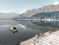 River water houseboats blue sky hills and water landscape and natural beauty in dal lake kashmir valley in india.