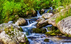 River waterfall stream rocks flow. Waterfall river stream rocks. Mossy rocks in river stream waterfall