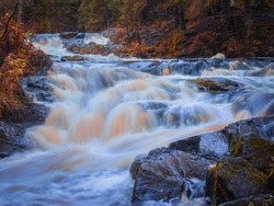 River with rapids in Karelia. Nature of Russia. Rocky section of Karelia river. Water vapor in middle of Karelia forest. Autumnal nature of outskirts of Priozersk. Landscape of northern Russia