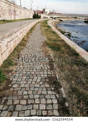 Riverside path. Cobblestone path along the river.  #1562594554