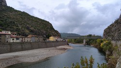 Riverside riverbed river with stones with cliffs of some mountains greenish bushes cloudy sky gray and a metal bridge