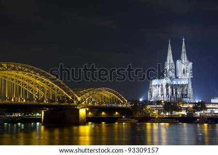 Riverside view of the Cologne Cathedral and railway bridge over the Rhine river in Germany at night