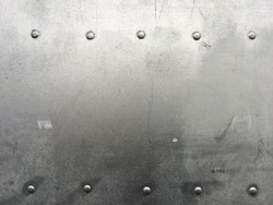 Riveted metal background, detail metal textured background from aircraft. Old grunge metal fragment of protective structure made of metal plates sheets assembled with button head rivets.