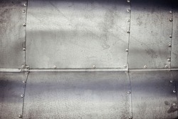 Riveted, sheet metal, waved, weathered surface abstract background image.