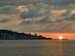 Rize is a touristic coastal port city near blacksea. sunset view of Rize city with reflection of sun on the sea.