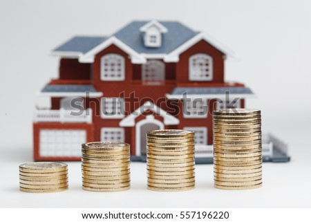 RMB coins stacked in front of the housing model (house prices, house buying, real estate, mortgage concept) #557196220