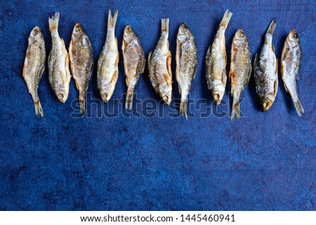 Roach -pattern of dry river fish on a blue wooden background. The view from the top. For bars and restaurants. Beer snack. Copy space.