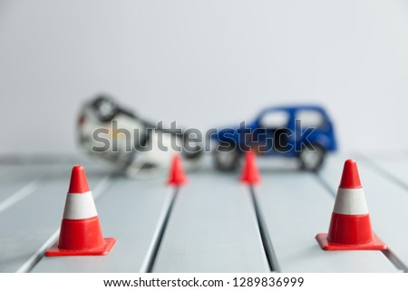 road accident with toy cars, two orange cones, blurred background #1289836999
