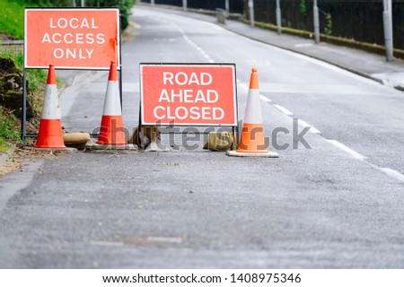 Road ahead closed and local access only sign and traffic cones #1408975346