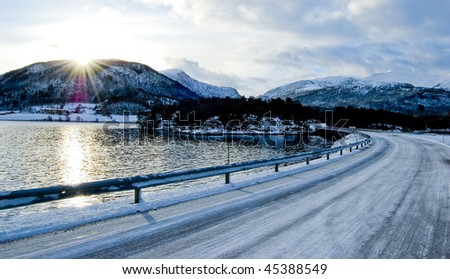 Stock Photo Road along seaside against sun in norway, winter