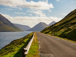 Road along the ocean on Kalsoy island, Faroe Islands, Kingdom of Denmark, North Europe. The road network on the Faroe Islands is highly well developed.