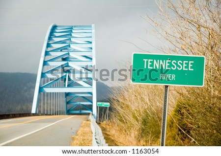 Road and Bridge Across River with Sign