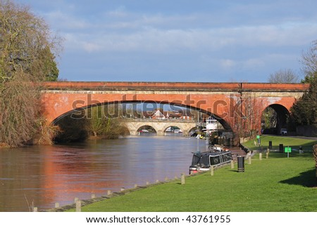 Road and Rail Bridges over the River Thames at Maidenhead, England with houseboat moored on the riverbank