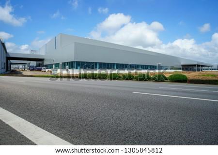 Road asphalt pavement and modern factory warehouse #1305845812