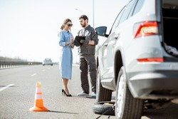 Road assistance worker signing some documents with woman near the broken car on the highway