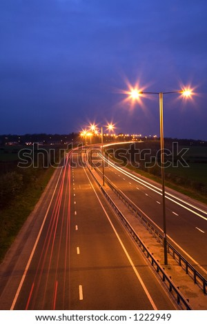Road at night with traffic trails and street lamps