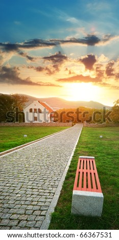 Road, bench, and house on the sunset. Landscape composition.