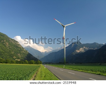 Road between mountains and a wind-driven generator