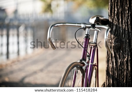 Road bicycle on city street, cycling in summer nature, vintage old retro bike, cycling or commuting in city urban environment, ecological transportation concept