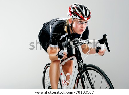 Road bicycle woman riding her bike and concentrating on winning the cycle race. full cycle gear and action as a real cyclist trains for fitness. isolated on grey. - stock photo