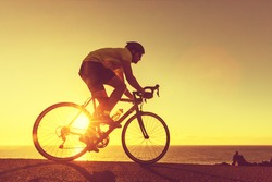 Road bike cyclist man cycling. Biking Sports fitness athlete riding bike on an open road to the sunset. Cyclist biking on road bike with sun flare. Active healthy sports lifestyle athlete cycling.
