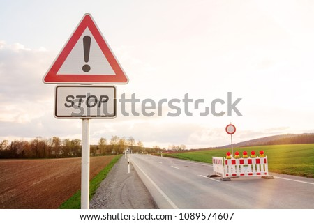 road block with street sign and warning lights on road at countryside