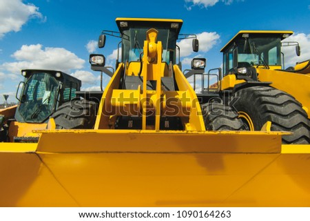 road-building machinery, tractors yellow excavators in the open air in working position