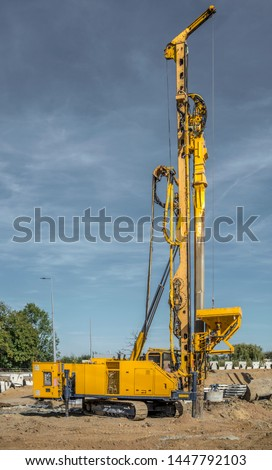 Road building with drilling machine. Drilling machine ready to drill piles on a road building site