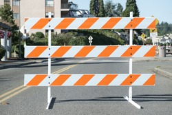 Road closed for construction barricade consisting of three horizontal bars alternating orange and white diagonal stripes and blurred background