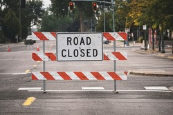 Road closed sign and barricade blocking street