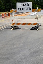 Road Closed sign on a battered traffic barricade, safety barrels and roadway construction, creative copy space, vertical aspect
