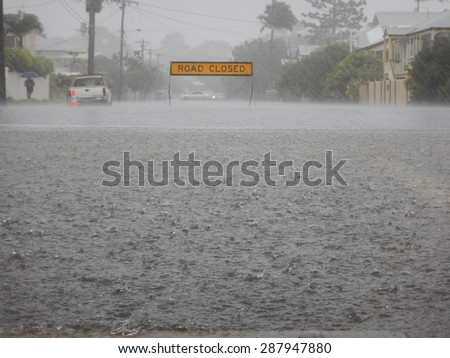 Road Closed sign on a flooded street in heavy rain. In the forground is a huge floodwater puddle with heavy raindrops.