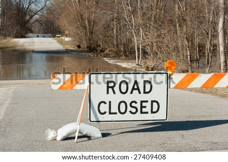 Road closed sign with flooded road and the Maumee river in the background.