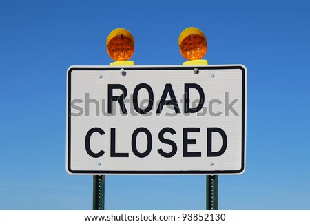 Road closed sign with orange lights against a bright blue sky