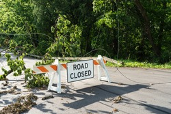 Road Closed sign with tree and power lines down after a big storm