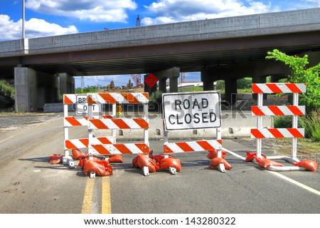 Road closed warning safety sign on traffic barriers on an American road near super highway bridge with improvement construction work site