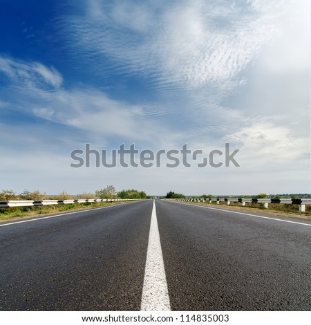 road closeup under cloudy blue sky