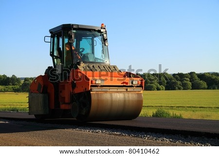 Road construction. Large rolling machinery paving a road to a distant city