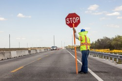 Road construction on the highway, Worker holds a stop sign to control the traffic