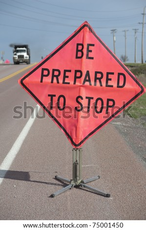 "Road construction sign ""Be Prepared to Stop"" with truck approaching, selective focus on sign"