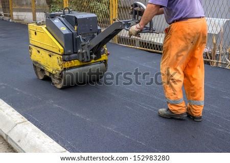 Road construction worker behind construction roller, leveling new asphalt on sidewalk