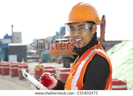 road construction worker  holding a  clipboard on the excavator background