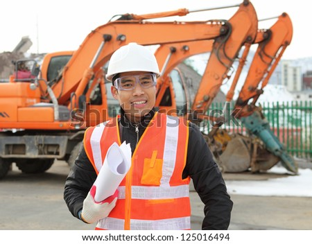 road construction worker holding blueprint and smiling