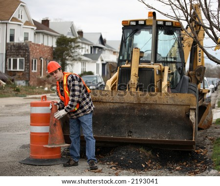 Road construction worker holding orange cone in front of an bulldozer. Residential area on the background.