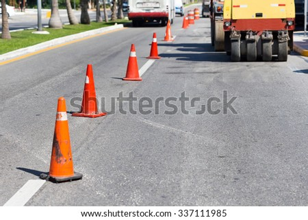 Road construction works. Traffic cones at tropical street warning about asphalt pavement works   #337111985
