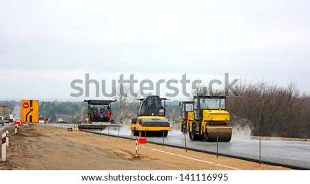 Road crew operate automatic asphalt spreader and steam roller follows