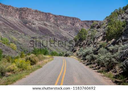 Road curves through the bottom of the Rio Grande Gorge in the Rio Grande del Norte National Monument near Taos, New Mexico #1183760692