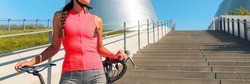 Road cycling in city cyclist athlete woman with bike wearing pink jersey outfit for sports biking on summer urban commute ride. Bicycle concept panoramic background.