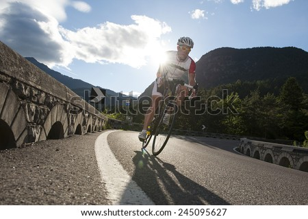road cycling in the mountains with sunrise behind